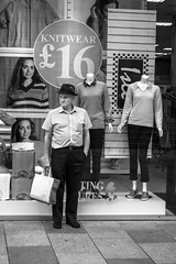 Knitwear (Howie Mudge LRPS) Tags: man pensioner shop sign pavement stand standing knitwear mannequin window clothes hat bored pose candid portrait blackandwhite blackwhite bw mono monochromatic monochrome street streetphotography streetlife urban urbanphotography cardiff caerdydd capital city wales cymru uk