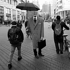 the hague (gerben more) Tags: thehague denhaag livingstatue people streetscene streetlife street netherlands nederland monochrome blackwhite umbrella suitcase