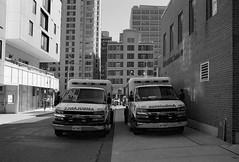 Ambulances (geowelch) Tags: toronto ontario urbanlandscape urbanfragments city blackwhite 35mmfilm kodakt400cn c41 pentaxesii 50mmf14supermulticoatedtakumar plustekopticfilm7400 newtopographics downtown