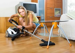 Woman Using A Canister Vacuum to Clean Hardwood Floor (mahihapter) Tags: vacuumcleaner clean cleaner woman cleaning domestic dust equipment female holding home house household housekeeping housewife housework interior maid one people person room vacuum vacuuming chores table sofa work working adult chore 2030 girl cleans happy fulllength standing cheerful spain