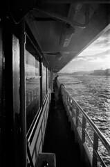 Evening Ferry (blueP739) Tags: olympus om4 om1n olympusom om3ti om2sp om10 om2n om1 om3 olympusom1 orange olympusplustekplustek7200om4 pussy plustek plustek7200 f kentmere100 sunset scanner water wave bw blackwhite monochrome tulip turkey turkishphotography istanbul boat contrajour perspective ilford id1111 id11 vivtar19mm eminonu