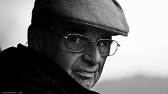 Over My Shoulder (Neil. Moralee) Tags: neilmoralee norway2016neilmoraleenikond7100 neil moralee man face stare glance glasses portrait close black bw mono monochrome eyes cap hat mature old senior penssion back age elderly cold outdoor people nikon d7100 white
