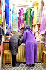 Decisions, decisions (halifaxlight) Tags: morocco fes medina women seller man vendor shop dresses fabrics dressmaker street feselbali purple green blue yellow display