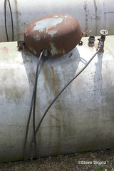 Propane tank tipping his hat. (Spike's Shoes) Tags: hello pictures summer usa abstract color colour art hat vertical wisconsin america grit found outside photography daylight midwest colorful humorous photographer exterior tank photos outdoor united steve north stock gritty images photographs cap american snapshots daytime states colourful picturesque greeting wi propane tipping imagery skjold grittiness cs19
