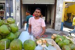 Coconut water salesperson (Daniel Incandela) Tags: street brazil man water brasil shopping saopaulo coconut tshirt fujifilm vendors rua25demaro xpro1