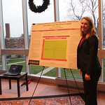 Student poses with her poster presentation.