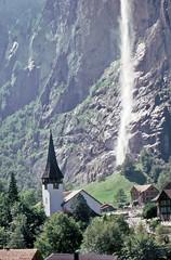 Lauterbrunnen village  church and  Staubbach Falls  1977 (D70) Tags: church 35mm waterfall 5 slide olympus falls 64 halfframe 1977 lauterbrunnen sept zuiko swizerland f35 kodacrome penf autozoom staubbach 50–90mm