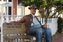 A sit-by-me statue of Sheriff Joe Perry (Gerald (Wayne) Prout) Tags: sitbymestatueofsheriffjoeperry staugustine oldjail cityofstaugustine stjohnscounty florida usa prout geraldwayneprout canon canoneos40d sitbymestatue sheriffjoeperry sheriff joeperry jail stjohns county attraction tourist prisoner jailer police lawenforcement magnolia