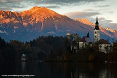 Sunset over Lake Bled (Ian Middleton: Photography) Tags: travel autumn trees sunset vacation cliff lake holiday mountains alps reflection building tower castle history tourism church water beautiful architecture clouds religious island evening still scenery europe european bell famous scenic eu tourist tourists architectural historic christian clear slovenia alpine touristy stunning bled backdrop former christianity popular fortress defense defence hilltop yugoslavia attraction shimmering eec clifftop slovenian slovene gorenjska slavic karawanke