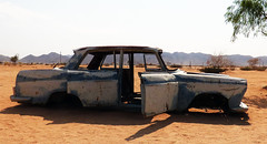 Namibia's Beauty:  40.  Broken down at Solitaire (ronmcbride66) Tags: namibia namibiasbeauty solitaire car abandonedcar wreckedcar bumpers fenders mountains desert roadsign