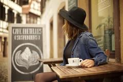 Jessica @Cafe Bretelles (Caropaulus) Tags: alpha7 blur cafe cafebretelles chapeau coffee cup girl hat petitefrance rokkor rue strasbourg street suspenders table lecellierdejess