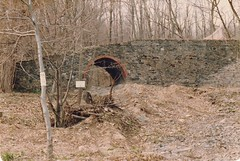 RUINS IN ROSENDALE IN 1984 (richie 59) Tags: ulstercountyny ulstercounty newyorkstate newyork unitedstates spring richie59 america outside townofrosendaleny townofrosendale oldphotograph oldphoto film 1984 photoscan 35mmfilm 35mm filmcamera filmphotography april221984 april1984 hudsonvalley midhudsonvalley midhudson nystate ny trees stonework archway hill weeds dirt ruins rocks stone