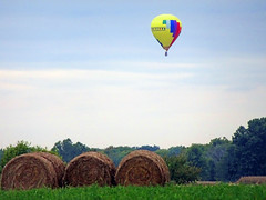 Balloon over Hay (Wits End Photography) Tags: blue red sky house reflection building green nature water pool field grass yellow clouds rural america circle landscape outside mirror illinois pond marine midwest colorful exterior view natural bright outdoor farm vibrant country agrarian rustic gray balloon lawn harvest scenic vivid structure american round vehicle airship hotairballoon homestead hay agriculture pastoral multicolored bale solitary picturesque grounds turf sod circular agricultural bold bucolic eyecatching countrified