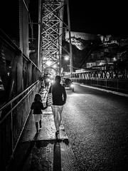 Bridge Crossing (Doug Knisely) Tags: street bridge bw portugal contrast walking crossing daughter mother olympus porto pedestrians littlegirl backlit carheadlights 1517 omdem5markii