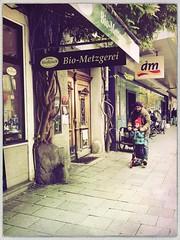 Bio-Metzgerei (Casey Hugelfink) Tags: munich mnchen haidhausen weisenburgerstrase metzger butcher bio biometzger biofleisch biomeat father son vater sohn roller glyzinie glycinia street streetphotography door doorway