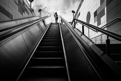 "the girl at the end of the escalator / ""Steppin' Out"" (zgr Grgey) Tags: 2016 20mm bw d750 nikon voigtlnder architecture escalator lines reflection street istanbul"
