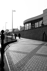 Making Waves (Richie Rue) Tags: nikond300 mono monochrome blackandwhite people walk walking prom promenade curves waves wavy lines building cobbles