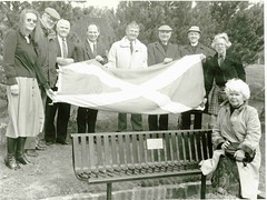 Photo of Mrs Jean Angus (seated) with representatives of seven organisations who erected a memorial seat to writer and broadcaster David Angus in the grounds of Stirling University.