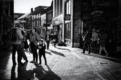 Drawn By The Light (h_cowell) Tags: mono monochrome bnw blackandwhite shadows street streetphotography candid noir silverefex panasonic gx7 shops shopping macclesfield cheshire uk people crowd walking striding texture appicoftheweek