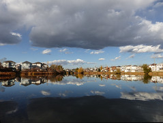 A narrow strip of light (annkelliott) Tags: autumn houses sky cloud sunlight canada calgary fall nature water clouds landscape pond scenery outdoor ominous alberta wetlands bridlewood urbanscene annkelliott anneelliott swcalgary fz200 22october2015 fz2003