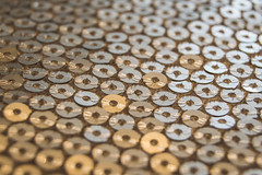 Sequins in Sequence (NVOXVII) Tags: macromondays hmm sequins rows lines stitch fabric cushion macro nikon closeup gold silver tones dof depthoffield artistic indoor furnishing sequence pattern thread