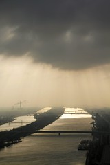Danube in the rain (stecker.rene) Tags: danube donau vienna rain sky clouds rays sunrays sunray ray sonnenstrahlen sun reflection water river bridge neue city stadt view aerialview canon eos7d tamron 18270mm austria light februar 2015
