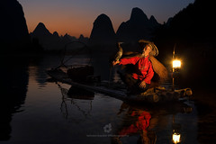 Cormorant Fisherman at Sundown, Yangshuo, China (fesign) Tags: adult bambooraft bird boat chinaeastasia chineseculture clearsky colourimage cormorant fisherman fishing fulllength gaslamp guilin horizontal karstformation lantern mountain onemanonly oneperson oneseniorman outdoors people photography reflection river riverli rurallife senioradult silhouette sitting sunrisedawn sunset traditionalclothing twilight twoanimals water woodmaterial xingping yangshuo