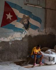 Fidel's Steady Gaze (Warriorwriter) Tags: socialism fidelcastro cuba lahabana cu havana vieja city travel castro fidel flag communism street people modern phone