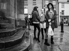 hanging around in a northern town (streetstory [is offline]) Tags: girls boots 28mm steps streetphotography ricohgr socialdocumentary wetpavement hairandbeauty manwithheadphones victorianstreetfurniture