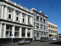 Dunedin. 19th century office buildings now converted to luxury city centre apartments. From the days when Dunedin was the largest city of New Zealand. Man on fire escape balcony.