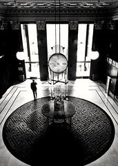 Lobbying (O Caritas) Tags: sanfrancisco california blackandwhite bw clock monochrome silhouette mobile businessman hotel entrance cellphone highcontrast lobby phonecall unionsquare westin revolvingdoor hotellobby westinstfrancis snapseed samsunggalaxysiii