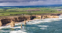 Weathered (Howard Ferrier) Tags: oceania australia waves countryside greatoceanroad helicopter green coast cliff transport rock landmass aircraft viewfromabove portcampbellnp tourism southernocean field beach ocean victoria limestone road sedimentaryrock island carpark rain clouds stack southwest places princetown au