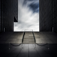 Enter the Void (One_Penny) Tags: duesseldorf germany medienhafen zollhafen zollhof architecture building canon6d city design modern photography town dsseldorf stairs staircase square squareformat lines clouds sky sinister symmetry symmetric entrance longexposure light tones void empty minimal