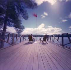 Who's on Deck? (george.bremer) Tags: kodak longexposure 6x6 algonquinhighlands blur c41 canada chairs deck dorset epson expiredfilm film filmphotographyproject flag fpp furniture lake margaretlake ondu ontario pinhole scan unicolor v750 vericoloriii vps vuescan wind