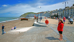 Aberystwyth on a fine day. (Minoltakid) Tags: uk sea summer beach june wales lady work geotagged fun person coast iso200 construction europe westwales unitedkingdom flag sony streetphotography eu diner oldbuildings 200iso aberystwyth lamppost promenade northbeach lifegaurd 1200 seafront dslr bandstand 27 attheseaside f11 ceredigion 27th rnli aber midwales beautifulday warmday constructionwork 2015 17mm hinterland welshcoast colourfulbuildings peoplerelaxing 1200th 170mm taged a900 f110 peoplehavingfun seasidephotography welshseaside rossevans sonydslra900 seasidecolours newbandstand minoltakid pdsdiner theminoltakid thewelshseaside rossdevans ceredigioncounty rnlilifegaurd atthewelshseaside thewelshcoast rnliperson rnlimember