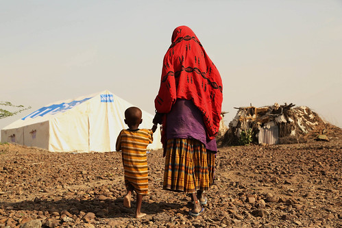 Dehabo Seyre grandmother of two, walks in to temporary emergency rub hall tent built by UNICEF