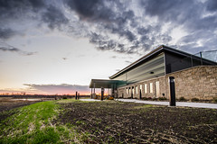 Baker Wetlands Discovery Center (denny.weinmann) Tags: new sunset sky building grass clouds landscape kansas lfk lawrenceks discoverycenter bakerwetlands sonyalpha rokinon a6000 southlawrence sonyimages douglascoks rokinon12mmf2