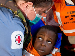 Royal Navy Medical Assistant from HMS Bulwark caring for a rescued child in the Mediterranean (Royal Navy Media Archive) Tags: africa rescue osmond hampshire help portsmouth landingcraft solas bulwark humanitarianaid lcu assaultship surfaceship safetyoflifeatsea opweald