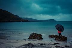 Staring at the Sea (neal1973) Tags: sea ocean north water rocks beach sand rain wet woman umbrella scotland mull isle blue red sad waves