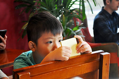 No phone, but... (Roving I) Tags: boys children brighteyes paper woodenfurniture cafes chairs coffeeshops concentration vincom malls danang vietnam