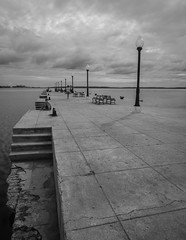 Sitting on the Wharf (buddythunder) Tags: travel light boy blackandwhite bw lamp clouds concrete grey sitting cuba steps perspective young wideangle wharf posts cuban cienfuegos crumbling cracking