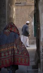 IMG_8723 (mariatarasoff) Tags: yemen sanaa old city souk brick mud stone people man woman walking pointofview perspective watching looking arab arabia muslim niqab hijab traditional clothing shawl veil thobe red blue white batik
