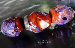 Rocks Sienna Violets (Laura Blanck Openstudio) Tags: openstudio openstudiobeads glass murano handmade lampwork beads bead set jewelry whimsical funky odd frit organic abstract earthy asymmetric colorful multicolor rocks nuggets pebbles stones art fine arts artisan artist made usa published winner show festival big lavender lilac purple violet grape shiny poppies coral sienna brick warm neutral black cream white copper green orange