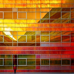 Autumn Tones (Paul Brouns) Tags: building buildings reflection reflections architecture architectuur abstract almere architektur square glass tainted foil colours color colourful colorful boy human geometry urban facade autumn tones orange yellow sunset straight holland netherlands flevoland
