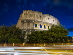 Blue Hour in the Eternal City (RobertCross1 (off and on)) Tags: street city longexposure trees urban italy rome roma history cars night clouds landscape ruins europe italia cityscape traffic dusk olympus it colosseum arena lighttrails bluehour romanempire omd lazio ancientrome flavianamphitheatre em5 1250mmf3563mzuiko