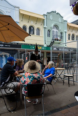 The Wizard has Arrived (Jocey K) Tags: newzealand christchurch buildings city signs architecture people street newregentst cafes chairs tables clouds shops mural streetart painting artwork hats sky wizard
