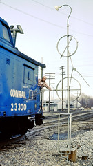 Trainman about to grab train orders from Conrail caboose  23300 at Willow Creek Crossing in Portage IN on 3-22-1982 (hardhatMAK) Tags: caboose flimsy kodachrome64 scannedslide conrail portageindiana 23300 willowcreekcrossing pickinguptrainorders 3221982