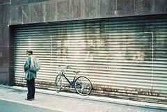 ( ourutopia) Tags: film adox colorimplosion 100 minolta himatic af filmphotography analog analogphotography expiredfilm bike woman people door rollingdoor store kawaramachi sanjo kyoto