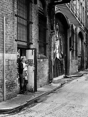 Northern Quarter #135 (Peter.Bartlett) Tags: manchester window unitedkingdom texting urbanarte door lunaphoto shutter girl candid uk m43 woman bw wall niksilverefex art people facade doorway drainpipe cellphone urban noiretblanc olympuspenf monochrome microfourthirds mobilephone streetphotography city sign blackandwhite graffiti peterbartlett