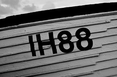 IH88 Boat (B/W) (DaveJC90) Tags: camera new wood old blue autumn light shadow sea sky blackandwhite bw cloud sun sunlight white black colour detail building slr classic beach water rain sign rock stone modern digital dark lens landscape grey bay boat town wooden movement nikon waves colours village view angle bright zoom cloudy wide wave sunny move sharp pebble rainy crop 1855mm 1020mm aldeburgh croped sharpness d5100